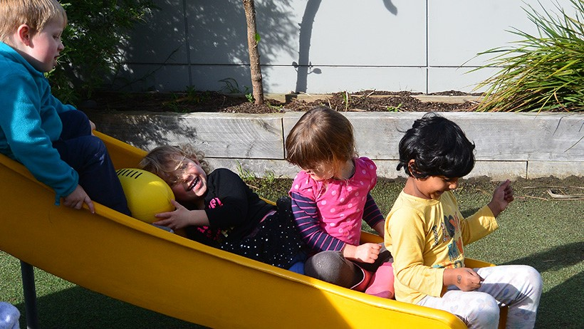 children smiling on slide at preschool
