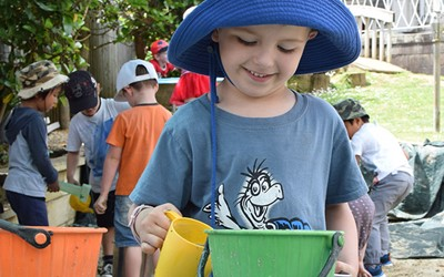 boy in hat with bucket and cup at childcare