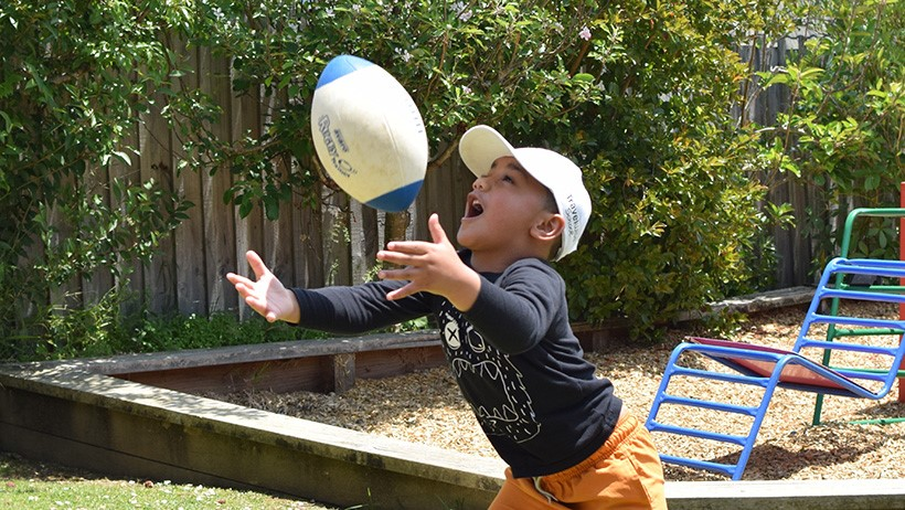boy catches rugby ball in playground at childcare