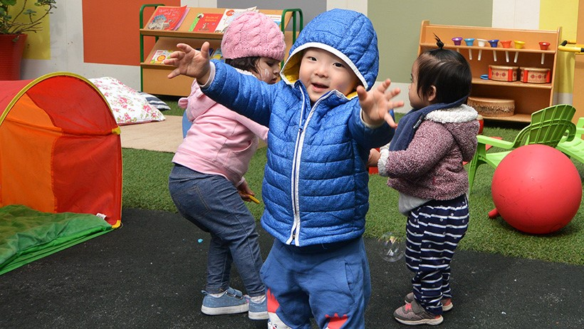 boy with arms outstretched at daycare