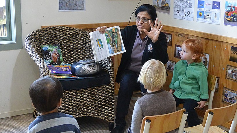 teacher reading a book to children at daycare