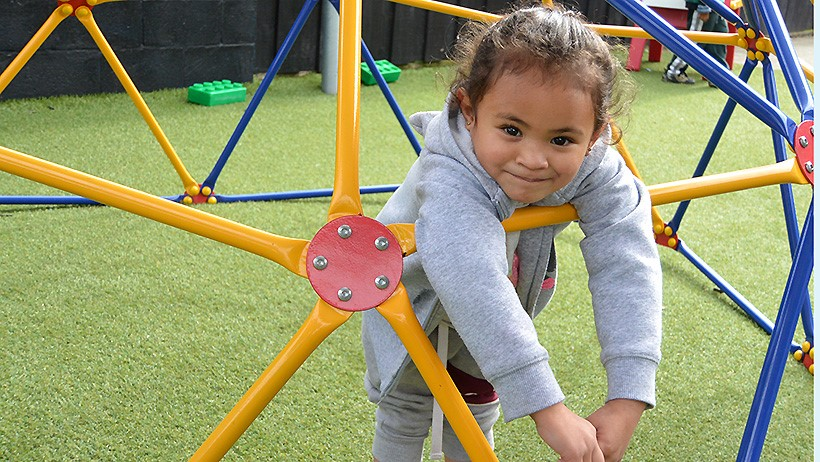 girl leaning on bars at childcare