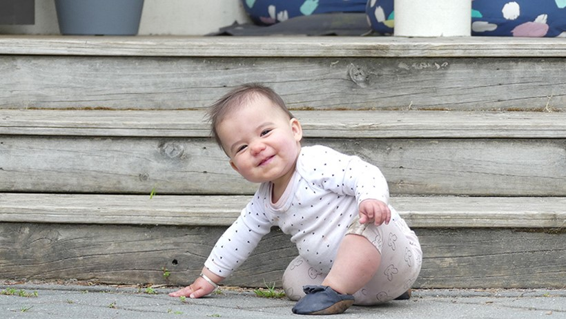 baby girl smiling crawling down steps at daycare